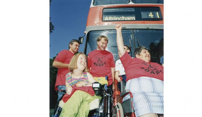 Five people, 2 are wheelchair users, are in front of a number 41 bus to Altrincham. They are smiling and looking to their left. Some of them have red t-shirts on with the word ADAPT under a wheelchair logo.