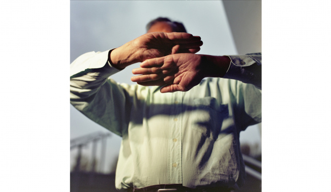 A man is photographed from the waist up. He is holding his hands up and out, with palms facing the viewer. His hands obscure his face. He is wearing a white/cream shirt and behind him are grey clouds.