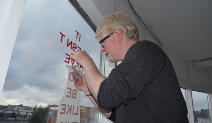 Aidan Moesby faces left toward a large window to which he is attaching red lettering. He wears dark rimmed glasses and a dark grey jumper