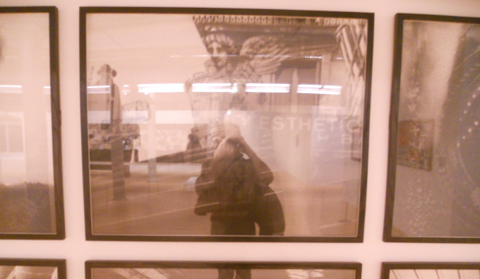 A sepia photograph of a person's reflection in framed photographs of buildings.