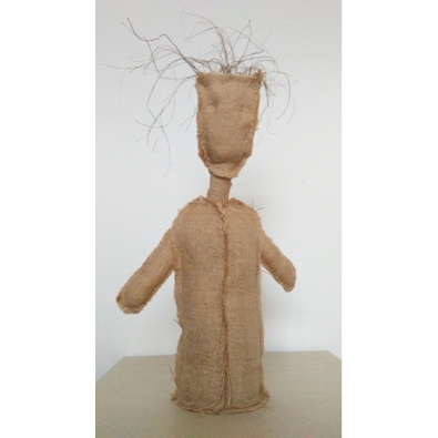 A hessian figure without legs stands against a light grey back ground. It's handless arms fall by its sides. The figure has a head without a face, and strands of wild wispy hair protrude from the top of its head.