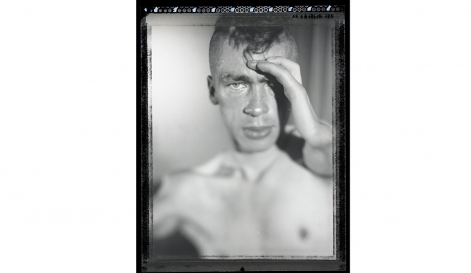 Black and white head and shoulders image of the great Mat Fraser. He is bare chested and is holding his left hand up to his forehead.  His head is shaved on both sides.