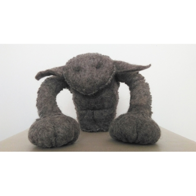 A grey symmetrical legless felted creature faces the camera. It has a pointed face with minimal features, wide horizontal leaf shaped ears and arms with large blob hands which reach down to the floor.