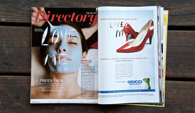 A centre spread of a womens' magazine on a wooden bench. On the left hand page is a woman with a face pack on, the words'Love Me' have been cut out of her face. On the right hand page is a pair of red high heeled court shoes.