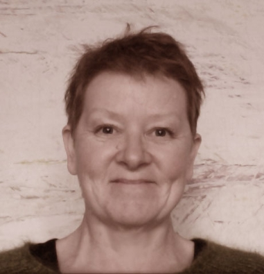 A head shot photograph of the artist Kruse. Kruse has white skin, and short cropped brown hair. She is facing the camera square on and smiling. She wears a mohair sweater and the photograph is in soft focus.