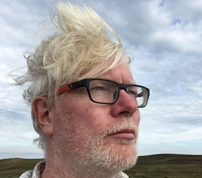 Aidan Moesby wearing dark rimmed glasses looks to the right. His hair is wind swept. He stands outside against a blue but cloudy sky