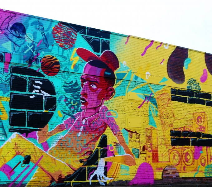 A brightly painted wall in graffiti, featuring an illustration of a young man wearing a baseball cap and short sleeved shirt and glove, catching a ball, against a backdrop of Birmingham landmarks.