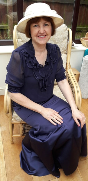 Image shows Processions participant Edel Slawson sitting in a chair, facing the camera and smiling. She is wearing a full length purple satin dress in an early 20th century style, with a cream hat with flowers.