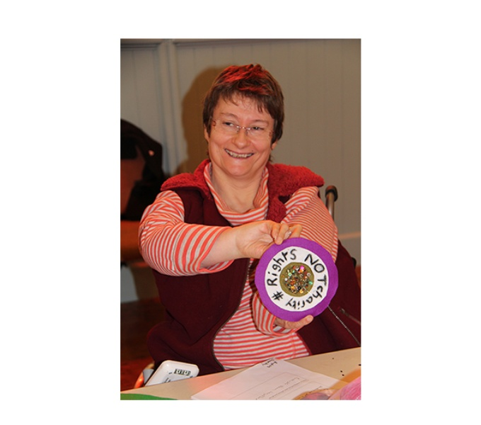 Disabled Artist Tanya Raabe-Webber smiles as she holds a purple and white rosette up to the camera