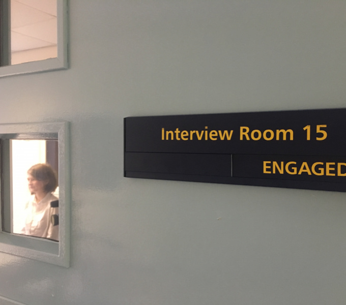 A photograph of a light grey painted wall with a large black rectangular sign on the right hand side of it with the words 'Interview Room 15, Engaged' on it in yellow. To the left are two small windows and through the lower window a woman is visible.