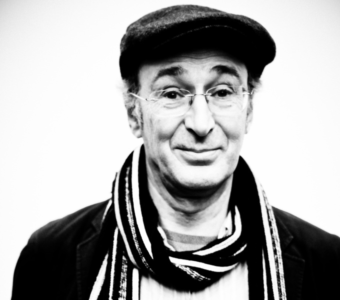 black and white photo of a clean shaven man, with a flat cap and striped scarf around his head.His dark eyebrows are raised as asking a question.