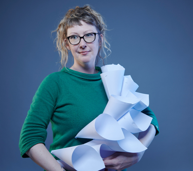 A photograph of Anna Berry wearing glasses and a green jumper and holding paper cones.