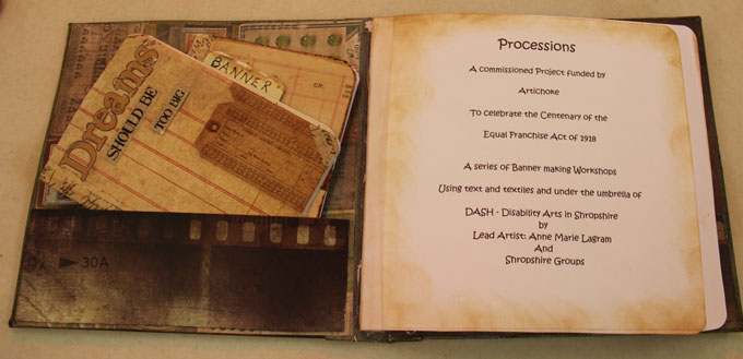 Photo of a handmade journal by Jean Green for the DASH PROCESSIONS project.  The inside cover has a pocket which is holding notepads, one says 'Dream should be too big'.  The next page tells us about the PROCESSIONS project.
