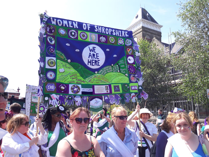 Images shows a close up of a larger crowd of women carrying a textile banner, made from purple, white and green fabrics. The main text of the banner reads 'Women of Shropshire' horizontally across the top. Beneath it reads We Are here in a circle. Below that are the shapes of hills with the names of women of noteembroidered on to them.