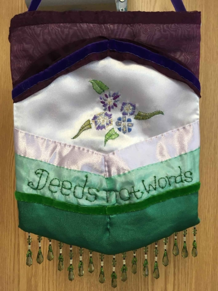 Embroidery pennant created by Rose Foran for the DASH PROCESSIONS project.  Using the colours of the suffrage movement, violet, white and green, the pennant is horizontally striped, using silk, satin and ribbon, it has flowers and 'Deeds not words' embroidered into the fabric. Delicate green beads finish the pennant at the bottom edge.