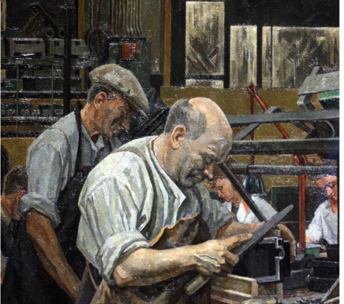 Inside a factory ,a bald headed man is working with a file smoothing a box like product, held in a clamp, behind him is another white shirted man in overalls wearing a flat cap, there are two other workers on the other side of the desk.