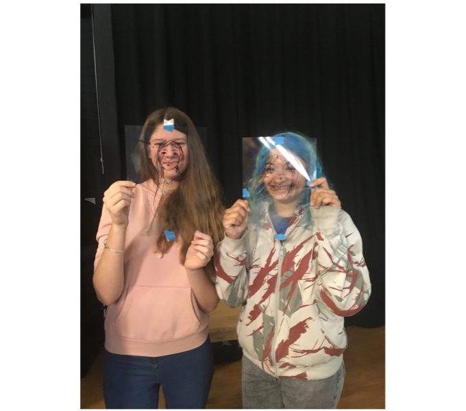 A photograph of two female students holding their acetate portraits up in front of their faces and smiling at the camera.
