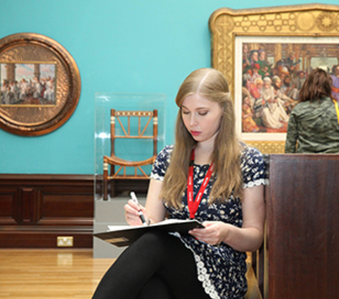 A young female is sitting and drawing inside the art gallery, behind her paintings and a chair can be seen.