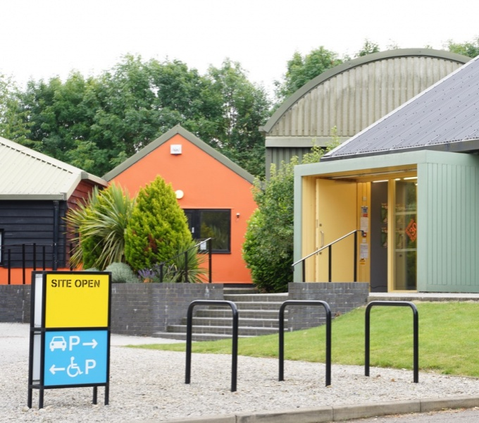 Exterior shot of Wysing Arts Centre. Foreground - bicycle racks and 'Open' sign, behind this are steps leading to orange, green and grey buildings, trees frame the buildings in the background.