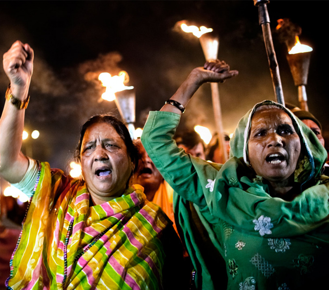 Two women shouting and waving their fists towards the camera, in saris, one green, one yellow, green and pink striped, they are part of a crowd of people marching in the night with tflaming torches held high.