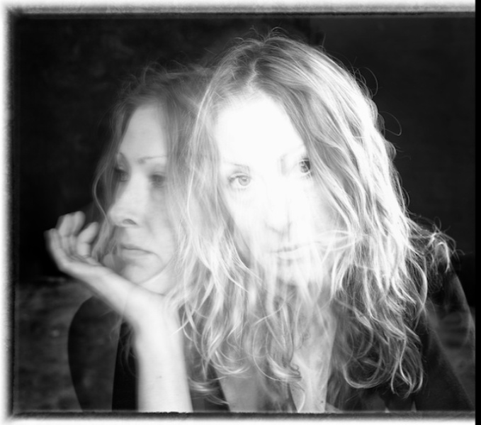 A black and whire double exposure headshot. Anna is looking to the right with her chin resting on her hand as well as looking at the viewer