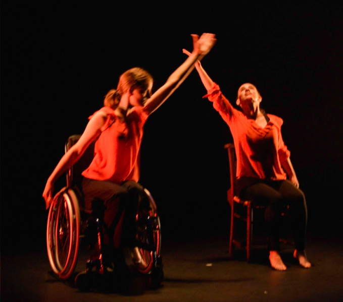Two female dancers, one sitting in a chair, one sitting in a wheel chair, both dressed in flame red tops, are making a cross in the air with their arms in the space between them.