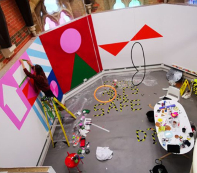 Inside the Chapel Arts Studio. An artist is attaching an arrow shape to a wall. There are other geometric shapes on the studio walls. Behind you can see the tops of the Chapel windows.