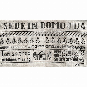 Sampler from the Staying Inn panel. White fabric with embroidered slogan; Sede in Domo Tua and wheelchair symbols below. Also embroidered are the phrases; I am so tired, #Millions Missing and Hem Yor Blessings with thanksgiving so they don't unravel.