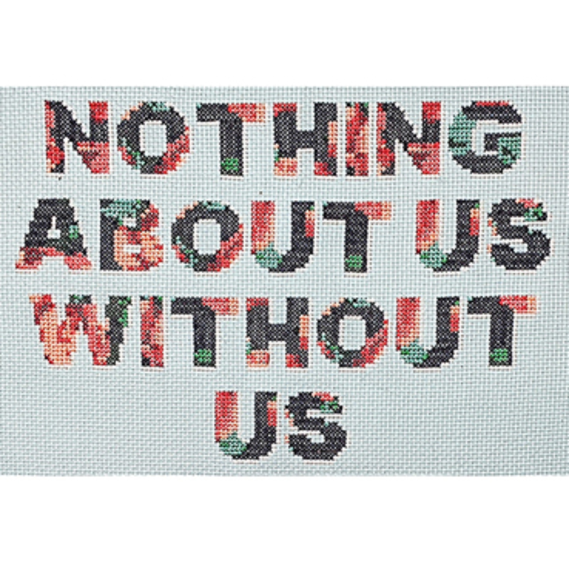 A cross-stitched panel. A white background with the words; Nothing About Us Without Us, stitched in bold capital lettering. The letters have a subtle floral pattern in navy blue, red and white vintage style.