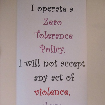 Printed words on narrow white paper read down the page: I operate a zero tolerance policy. I will not accept any act of violence, abuse, threat or intimidation.