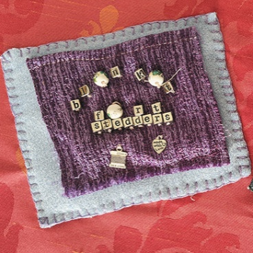 A pale blue square with smaller purple one stitched above. There are small square lettered beads attached spelling out 'blanket fort stedders.' Besides this, a small rectangular piece of denim with an embroidered leaf-like patch in gold embroidery.