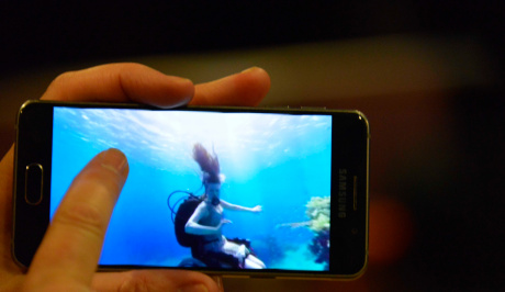 A left hand is holding a mobile on which Sue Austin is seen underwater swimming in her wheelchair with scuba tanks on her back. the sea around her is beautiful cyan blue with her dark ponytail hair flowing up into reflected sunlight.