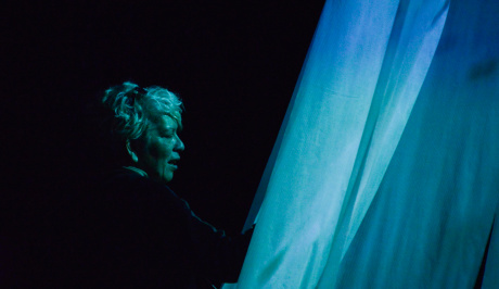 Against a black background, a womans side on face is lit with blue cyan light with the pieces of stretched fabric also lit with projected light, in front of her face, on the right of the photo.
