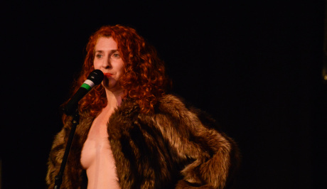 A long, wavy red-haired woman stands up to the mike,wearing an open fur coat and nothing else