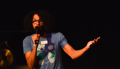 A black haired man in a blue and white t-shirt  hold the mike in his hand and raises his other arm and hand questioning