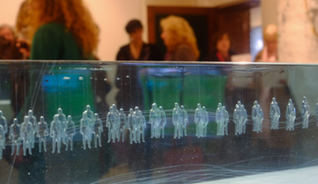 A photograph of a section of a long glass cuboid with many regularly spaced figures suspended upright within it. In the background, visitors observe the exhibition.