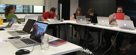 Image shows four training delegates at QUAD, sat at tables and discussing images laid out on the table before them. There are also laptops on the tables.