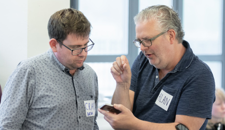 Cultivate mentor, Craig Ashley, deep in conversation with mentee, Alan Hopwood. They are both looking at a mobile device.