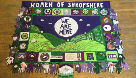 Banner created for the centenary of the 1st votes for women. 'WOMEN OF SHROPSHIRE' in felt letters at the top, 'WE ARE HERE' in felt letters, then the Shropshire hills in green felt below. Felt hands in purple, white and green surround the banner.