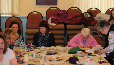 five women sit around a table full of bits of sewing materials, working on the banners for the processions.