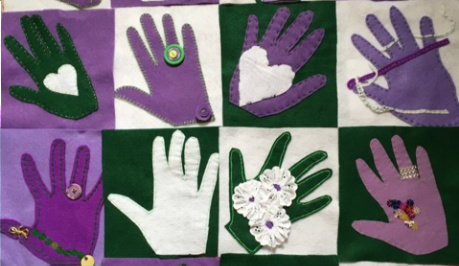 A piece of appliqued fabric, with cut out hands and symbols sewn on in the suffragette colours of white, purple and green.