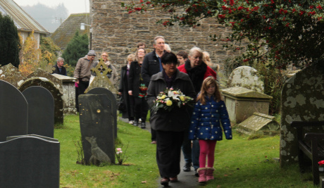 A photograph of a procession walking along a narrow path through a graveyard. The woman at the front is carrying flowers.