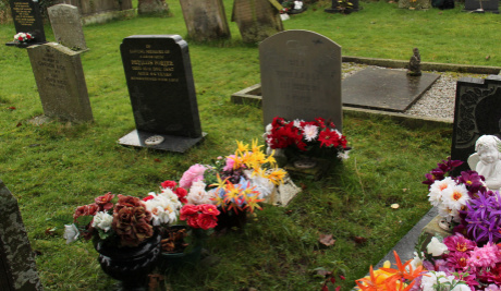 A photograph of Bill Lock's grave surrounded by other gravestones. In front of his gravestone is a row of different coloured flowers.