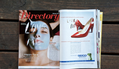 A centre spread of a women's magazine on a wooden bench. On the left hand page is a woman with a face mask on. The words 'Love Me' have been cut out of her face. On the right hand page there is a pair of red high heeled court shoes.