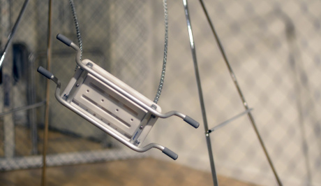 Through the blurred lines of close up netted fencing, a childs metal swing seems to be suspended in the air mid swing