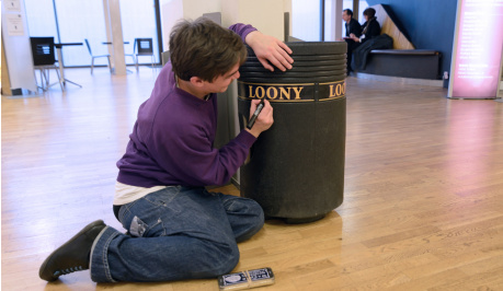 A young man is half sitting, half kneeling on the floor, dressed in blue jeans and and a purple jumper he is writing on a black,municipal type of litter bin, in gold capital letters  it spells out the word LOONY