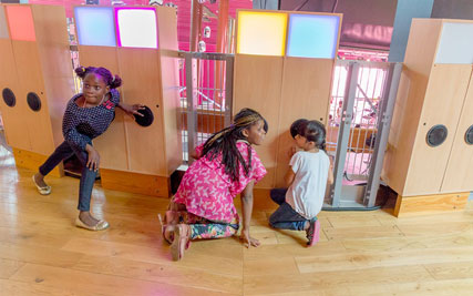 Three children are crouching listening to speakers which are encased in large wooden boxes.  The boxes have different coloured lights at the top.