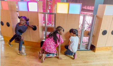 three young children with black hair are listening , crouched with ears to the black, round ear speakers on the wooden panels, with square lit squares in yellow, cyan, pink and blue at the top of the wooden panels.