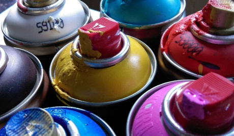 Assorted used spray cans in pink, yellow, blue , red and white grouped together with paint dripping from the nozzles.
