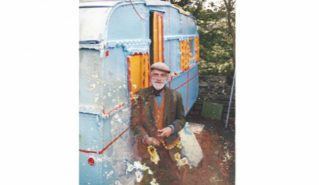 An old photograph of Bill Lock leaning against a light blue and yellow caravan